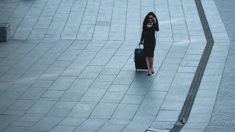 Woman walking with suitcase at street. Woman taking off sunglasses outside Live Action