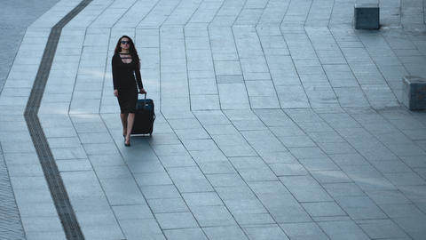 Woman walking with luggage at street. Woman looking away with suitcase at street Live Action