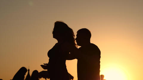 Super slow motion - couple silhouettes learning how to dance at sunset Live Action