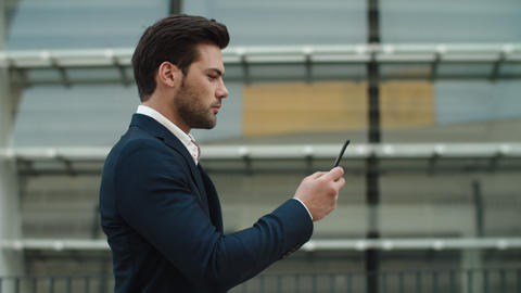 Side view businessman using phone. Businessman walking in luxury suit outside Live Action