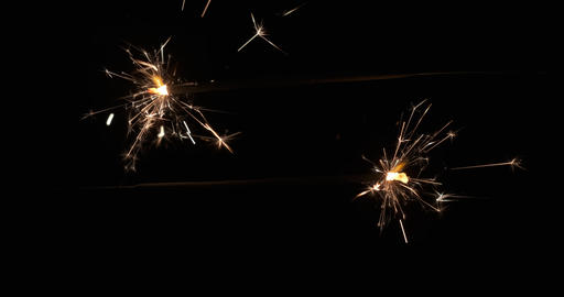 Close-up of sparklers burning and sparking in the dark. Two sparklers sticks are Live Action