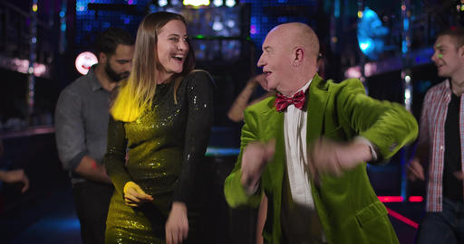 Portrait of cheerful senior Caucasian man and young pretty woman dancing in Live Action