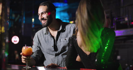Cheerful young Middle Eastern man taking cocktail and talking with bartender in Live Action