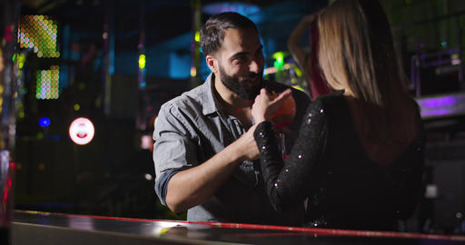 Handsome Middle Eastern man giving cocktail to young elegant Caucasian woman in Live Action