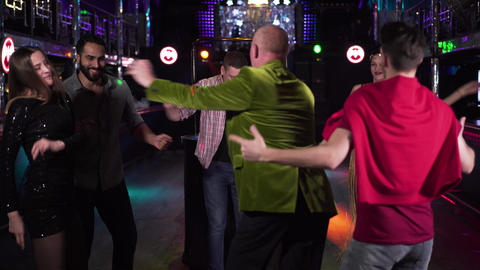 Group of young multi-ethnic people dancing around cheerful elderly man in night Live Action