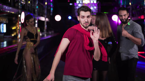 Portrait of young handsome Caucasian brunette man dancing in night club Live Action