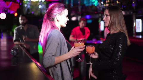 Charming Caucasian women dancing with cocktails at bar counter when men of Live Action