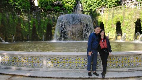 Asian couple gets souvenir photo at famous Roman fountains of Tivoli in Lazio Live Action