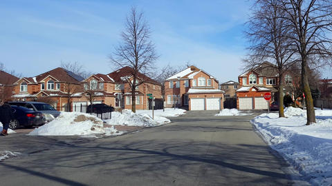 Pedestrian Walks on Sidewalk along Road in Residential Suburban Area in Winter With Heavy Clothing. Live Action