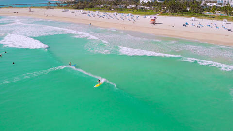 Aerial flight Miami Beach waves and surfboarders Live Action
