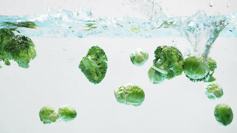Green Vegetables Falling into Water Footage