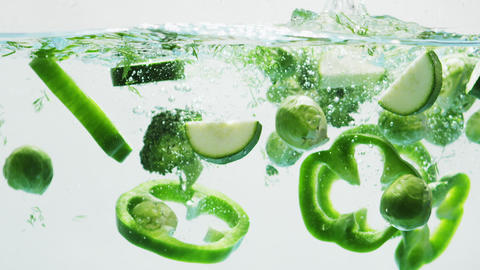 Green Vegetables Slices Falling into Water Live Action