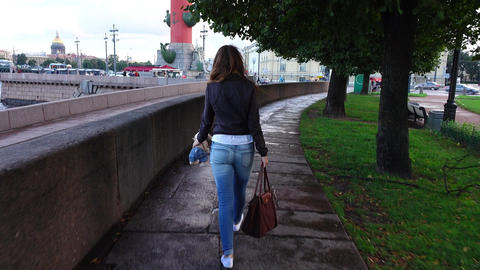 Young woman stroll at Neva River embankment, Spit of Vasilyevsky Island garden Footage