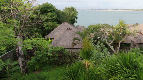 Flight of a drone over a tropical cottage village on the seashore Live Action