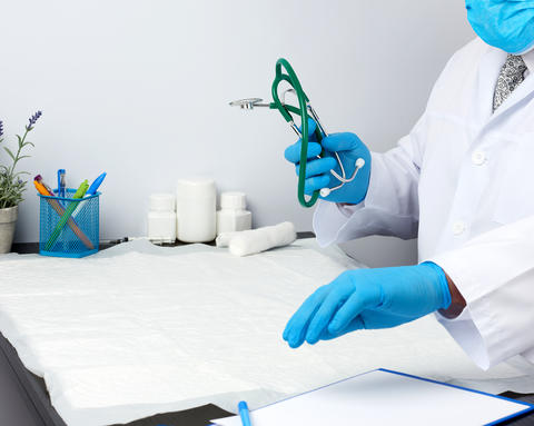 doctor in a white medical coat sits at a table and holds a green Fotografía