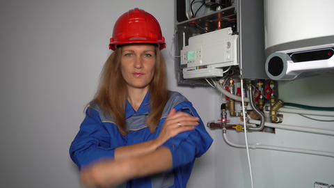 Playful model woman with helmet pretending as technician specialist gas boiler Live Action