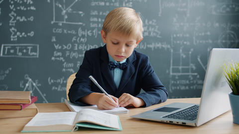 Young genius studying science at school writing in notebook with serious face Live Action
