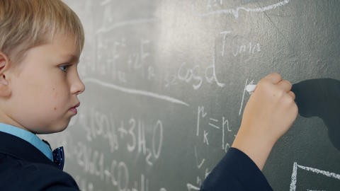 Slow motion of smart schoolboy writing formulas on chalkboard studying alone Live Action