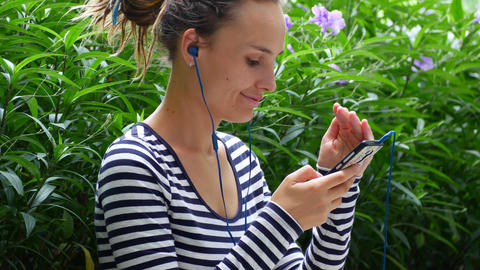 A young woman listens to music and communicates with friends on the Internet Live Action