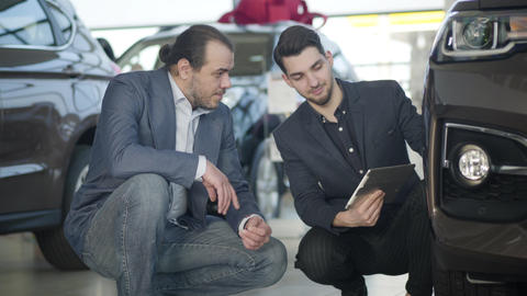 Portrait of Caucasian dealer and customer sitting next to vehicle in dealership Live Action