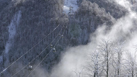 Ski elevator moving over snowy mountain forest in lowland. Drone view ski lift transporting skiers Live Action