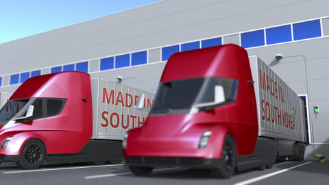 Modern semi-trailer trucks with MADE IN SOUTH KOREA text being loaded or Acción en vivo