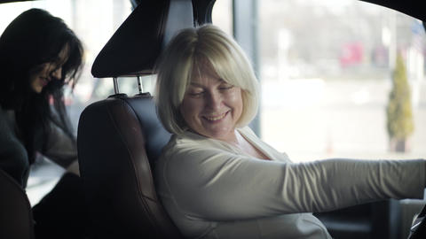 Senior blond Caucasian woman looking around inside new automobile as her young Live Action