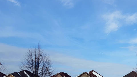 Distant View of Airplane Flying in Blue Sky Over Residential House Buildings. Commercial Plane Fly, Live Action