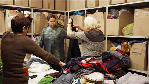 volunteers sort old clothes on table in storage with racks Acción en vivo