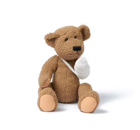 funny vintage brown curly teddy bear with rewound paw with white Fotografía