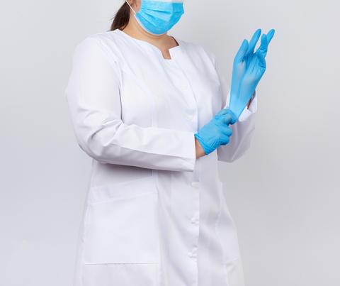 medical doctor in a white coat and mask puts on medical hands la Fotografía