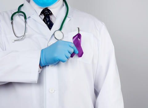 male doctor in a white coat and tie stands and holds a purple si Fotografía