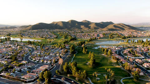 Aerial view of golf course surrounded by town houses and luxury villas during Live Action