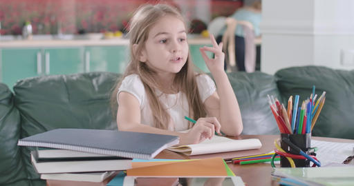 Pretty Caucasian schoolgirl sitting at the table, gesturing i got an idea, and Live Action