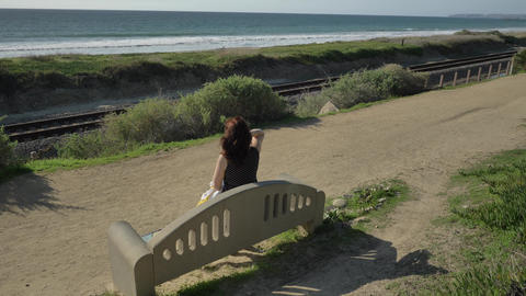 Woman happy Beautiful sunny summer Day sitting on the bench making hair at ocean Live Action