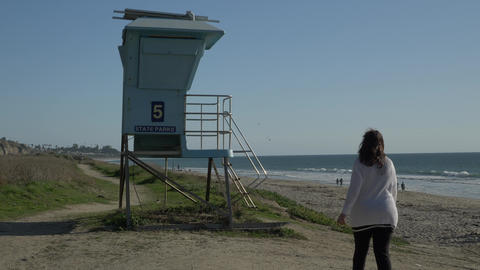 Woman walking to lifeguard tower and waving at summer day . Travel Vacation Live Action