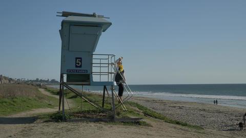 Woman standing at lifeguard tower and waving at summer day . Travel Vacation Live Action