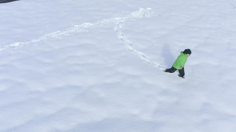 Man in green down jacket walks away on white snowdrift at winter. Man falling in snowdrift aerial Live Action
