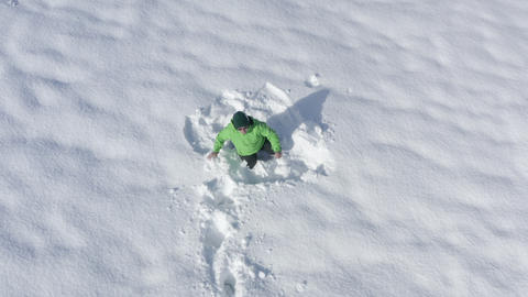 Cheerful man scared and runs away on white snowdrift at winter running walk. Man falling in Live Action