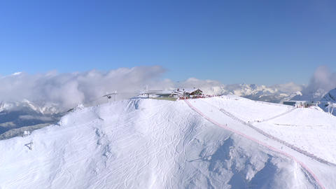 Aerial view from above winter mountain resort. People skiing and snowboarding on snow slope in Live Action