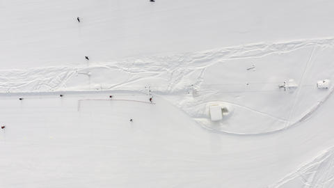 Top aerial view ski lift for transportation skiers and snowboarders. Drone wide view people riding Live Action