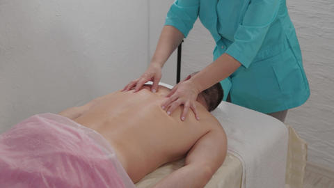 Female massage therapist doing a relaxing massage to a man in a massage parlor Live Action