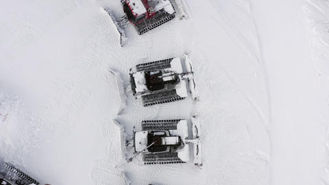 Snowcat standing on snowy parking lot at winter ski resort in mountain. Top aerial view from drone Live Action