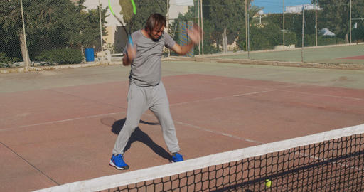 Male athlete playing tennis on outdoors. The ball hits the net, the athlete is Live Action