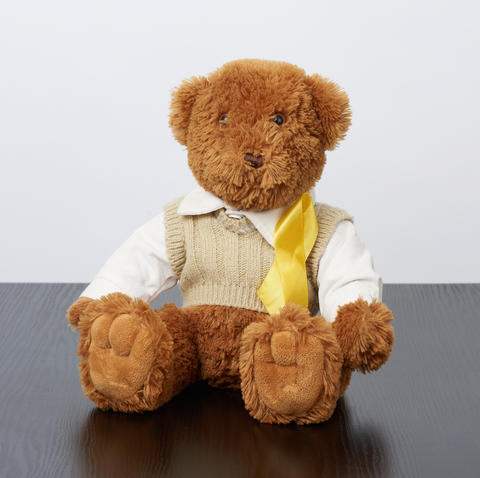 brown teddy bear sits and a yellow silk ribbon on a black wooden Fotografía