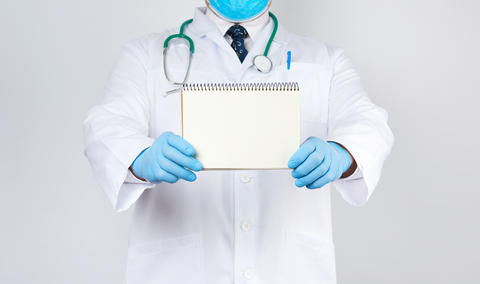 male doctor in a white coat and medical blue gloves holds a note Fotografía