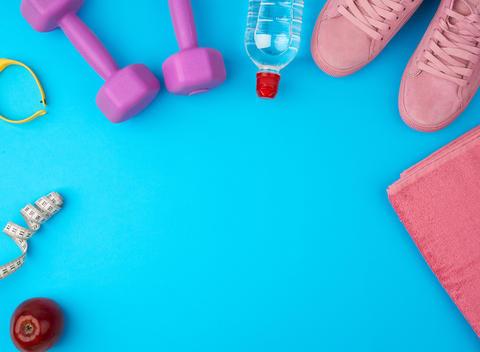 plastic purple dumbbells, sportswear, water, pink sneakers on a Fotografía
