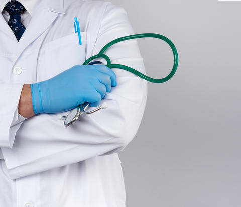 adult male doctor in a white medical coat stands and holds a gre Fotografía