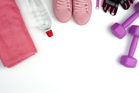 pair of pink leather sneakers, plastic dumbbells and gloves for Fotografía