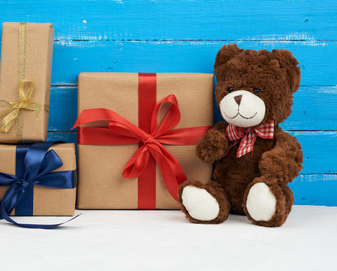 cute brown teddy bear sits on a blue wooden background and gift Fotografía